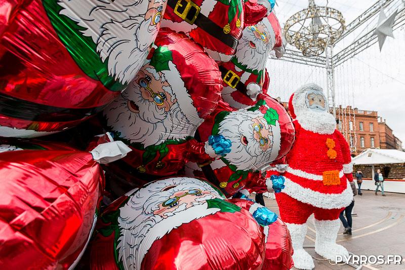 Les ballons de Père Noël côtoient la figurine du Père Noël géant dans les allées du Marché de Noël de Toulouse