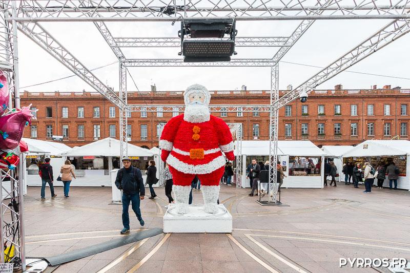 Au milieu de la place du Capitole le Père Noël géant veille sur les visiteurs du Marché de Noël