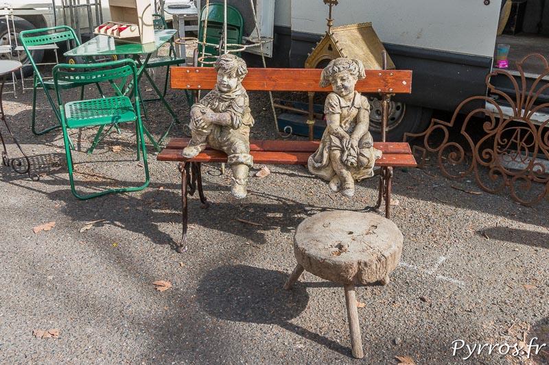 Des statues d'enfants reposent sur un banc et observent les visiteurs
