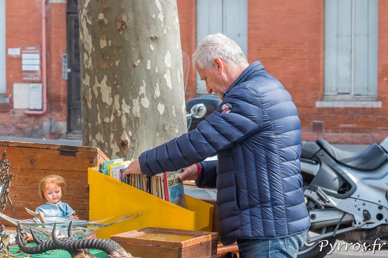 Un homme cherche une BD aux brocanteurs des allées