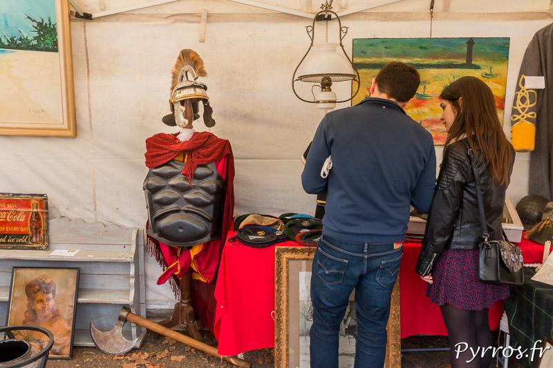 Un costume de centurion semble observer des visiteurs de la brocante