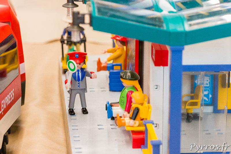 Le chef de gare guide les voyageurs qui embarquent dans le train Playmobil