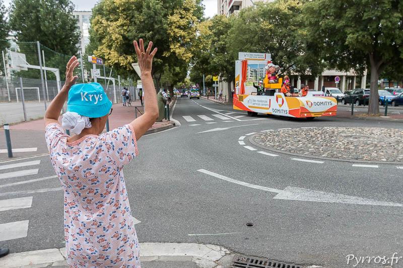 Une spectatrice lève les bras pour obtenir des goodies lors du passage de la Caravane Publicitaire du Tour de France
