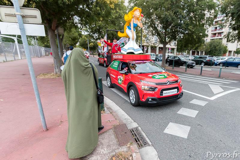 Une habitante du quartier de Bagatelle observe le passage des voitures du Parc Astreix présentes sur le Tour de France