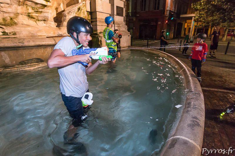 Un patineur arrose ceux qui souhaitent remplir leurs pistolets à eau
