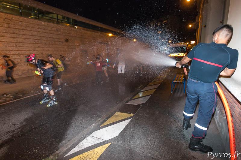 Un pompier arrose les patineurs qui passent devant la caserne