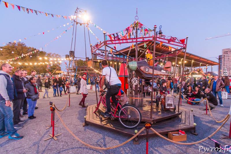 Un papa propulse un manège de la piste des Géants à l'aide d'un vélo